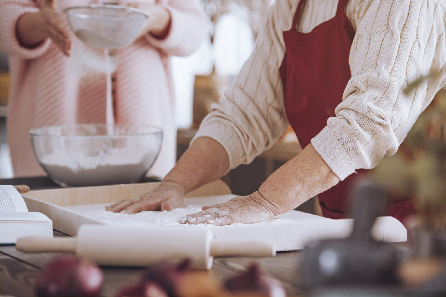 Close-up of person making cake on wooden board on countertop with rolling pin