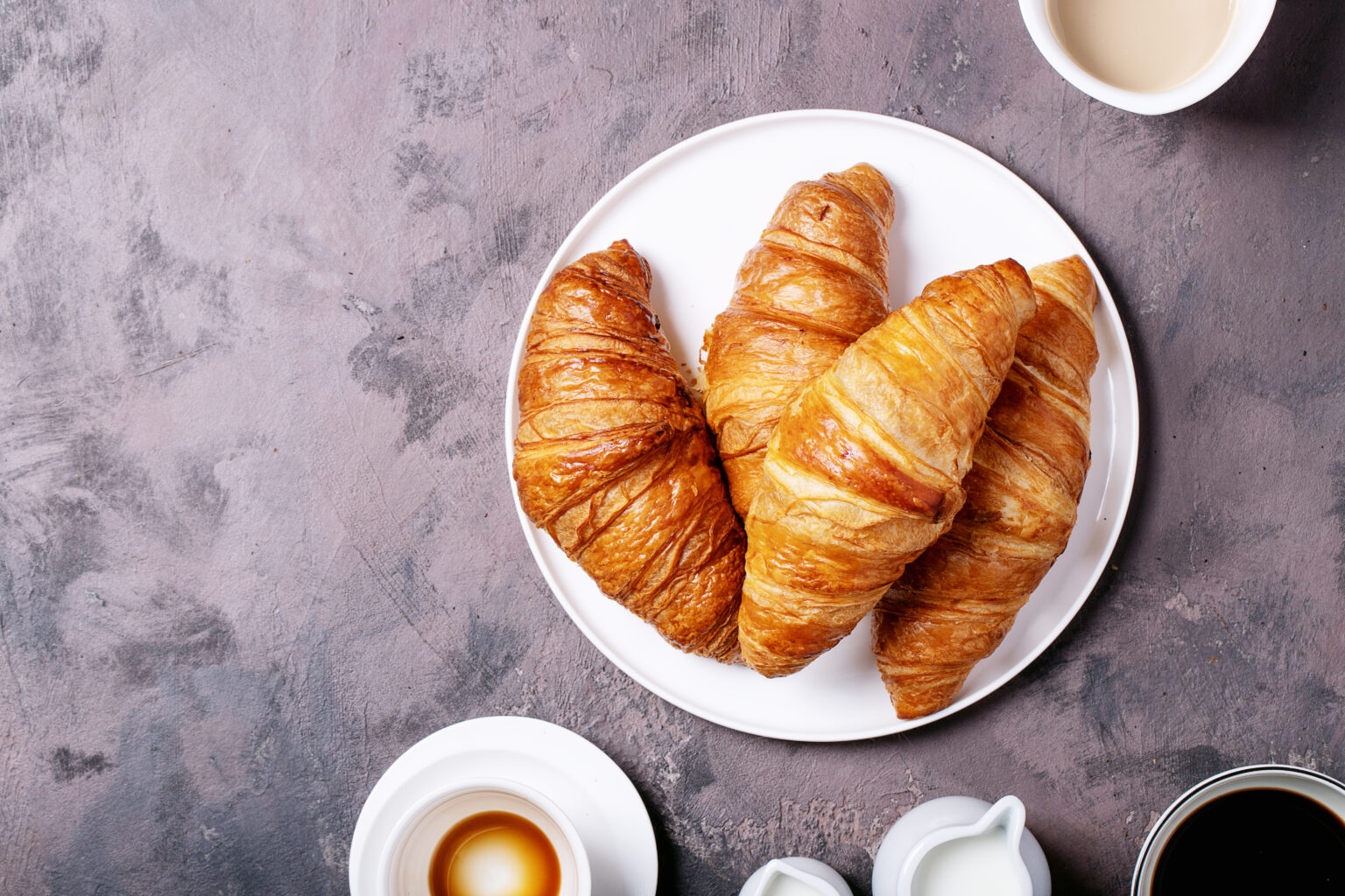 Fresh coffee in white ceramic cups served with croissants over brown texture brown background. Top view, flat lay