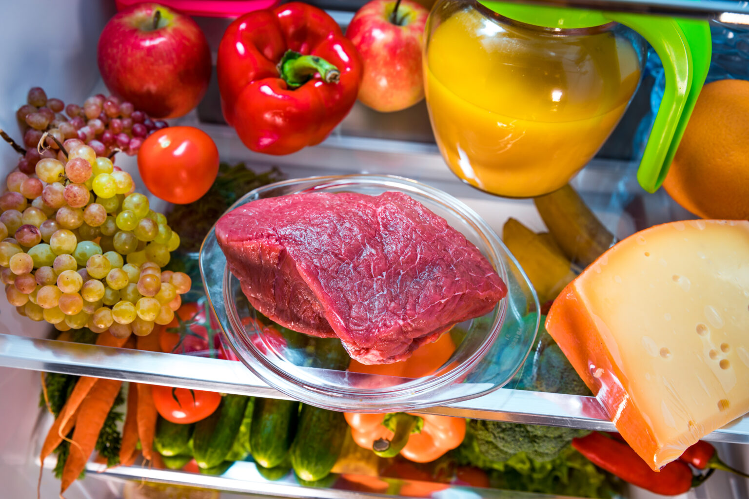 Fresh raw meat on a shelf open refrigerator