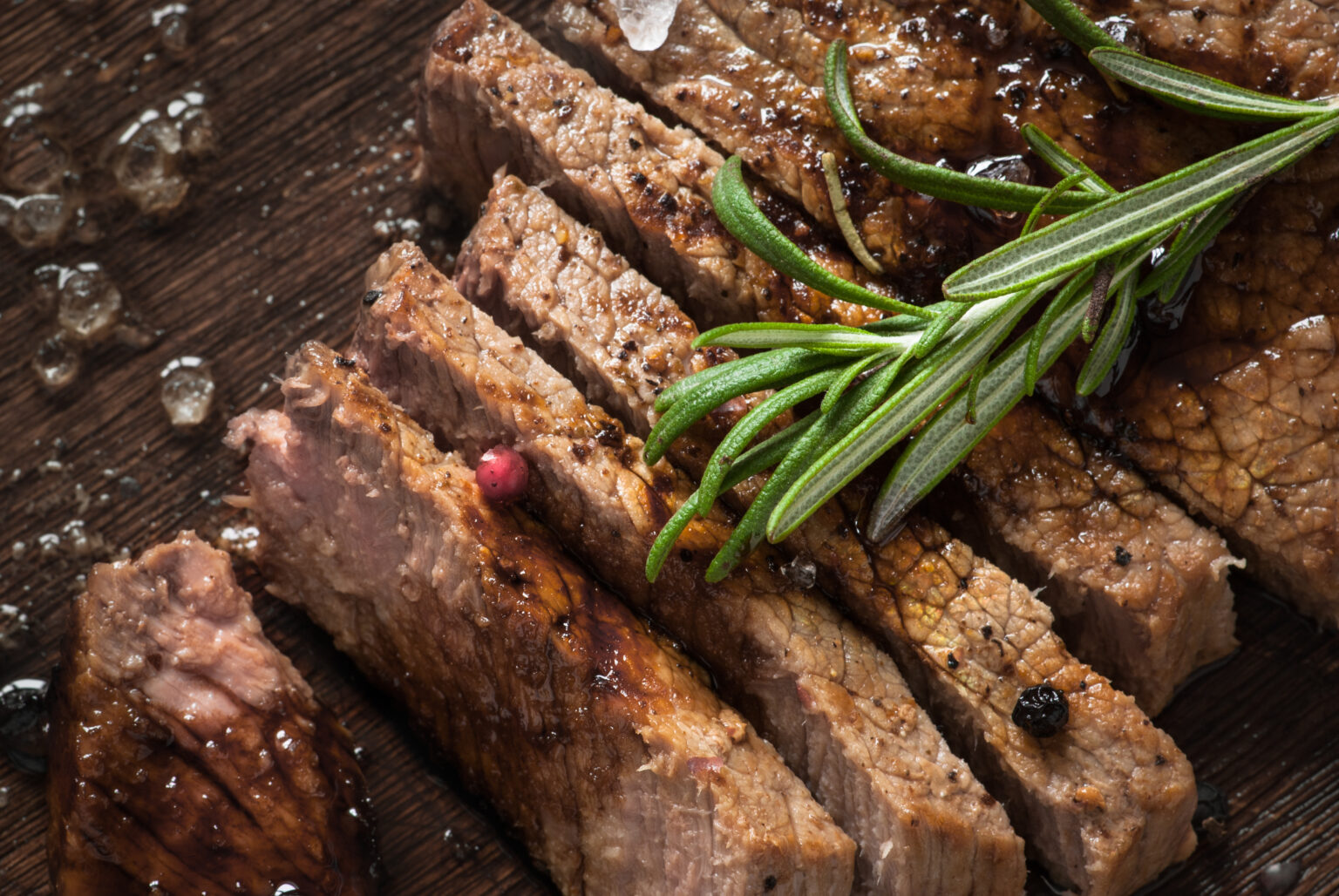 Sliced meat. Grilled beef steak on wooden cutting board. Top view.