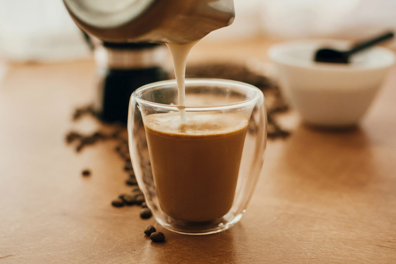 Pouring milk into coffee in glass cup on background of roasted coffee beans, grounded coffee, geyser coffee maker on wooden table. Making latte or cappuccino