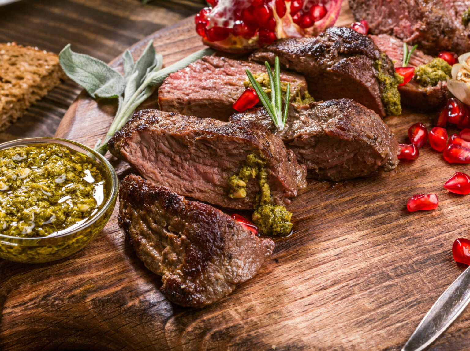 Kangaroo meat steak with green pesto and pomegranate on wooden cutting board. Helthy holiday food concept. Selective focus.