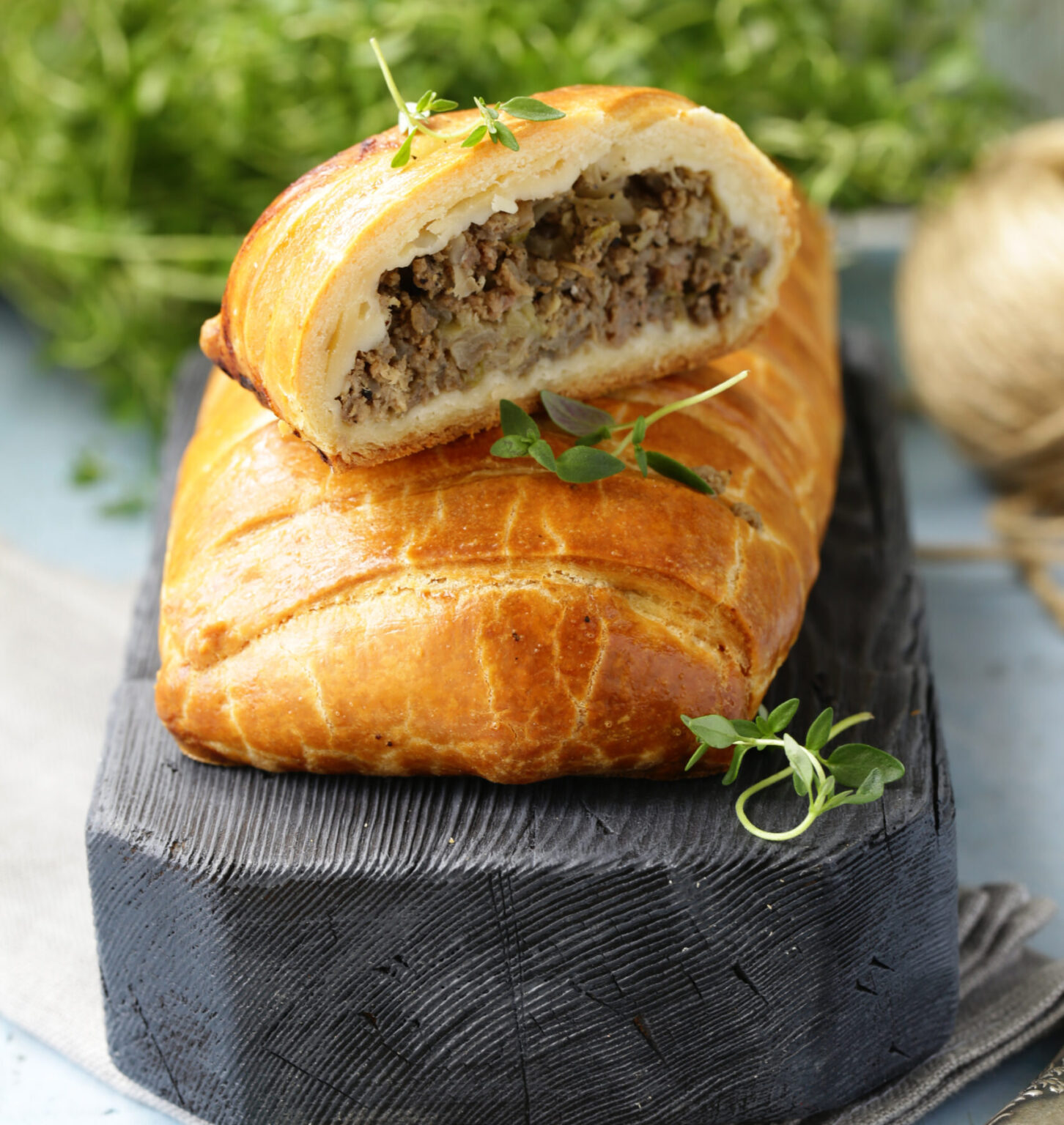 puff pastry pie with meat on a wooden board