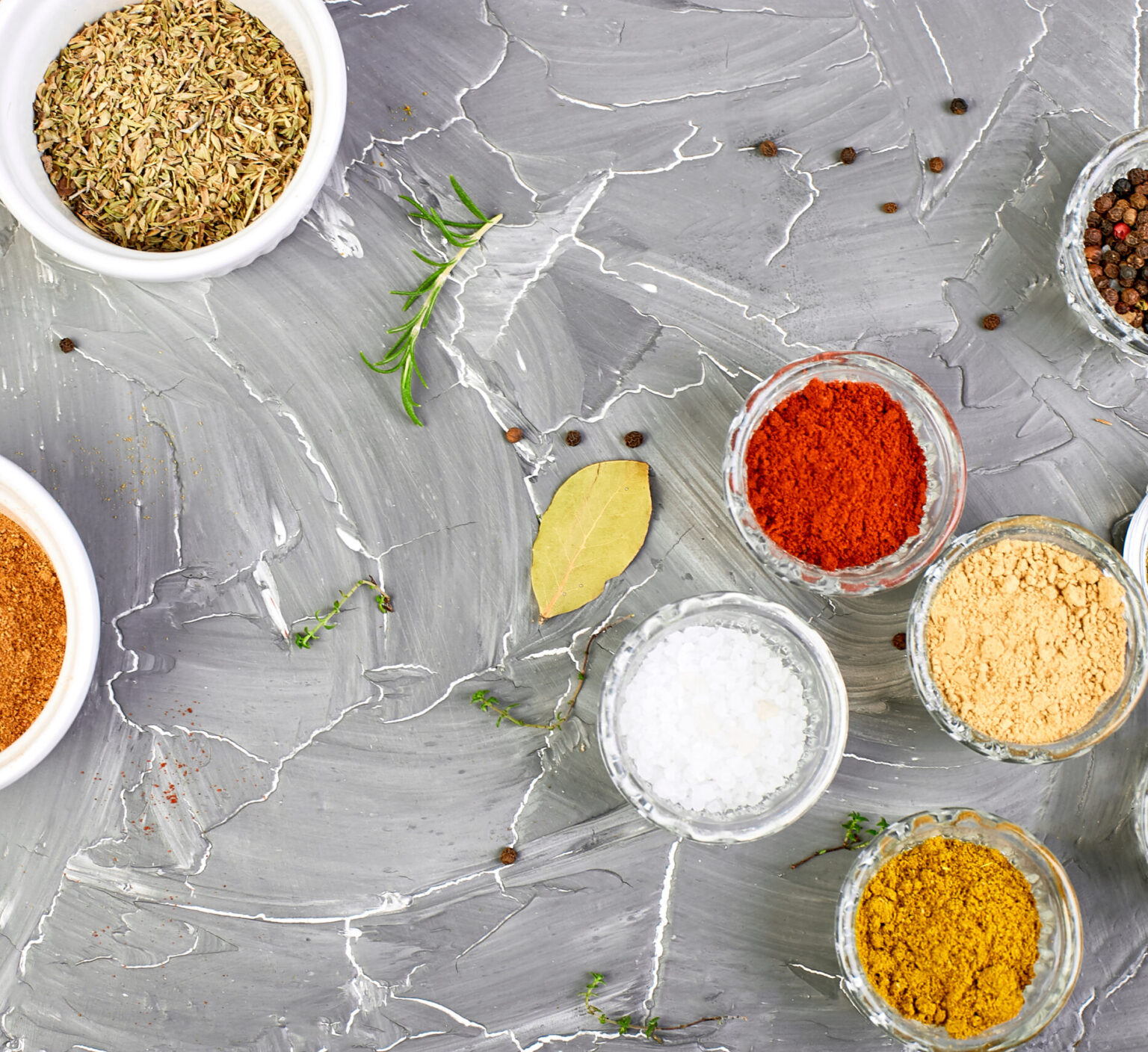 Seasoning background. Spice and herb seasoning with fresh and dried herbs and spices in bowls. Colourful various herbs and spices for cooking on grey background. Top view. Copy space.