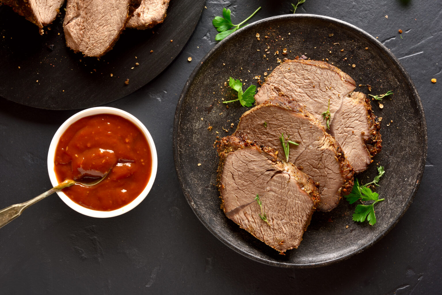 Roasted beef on plate over dark stone background. Tasty cooked beef with sauce. Top view, flat lay