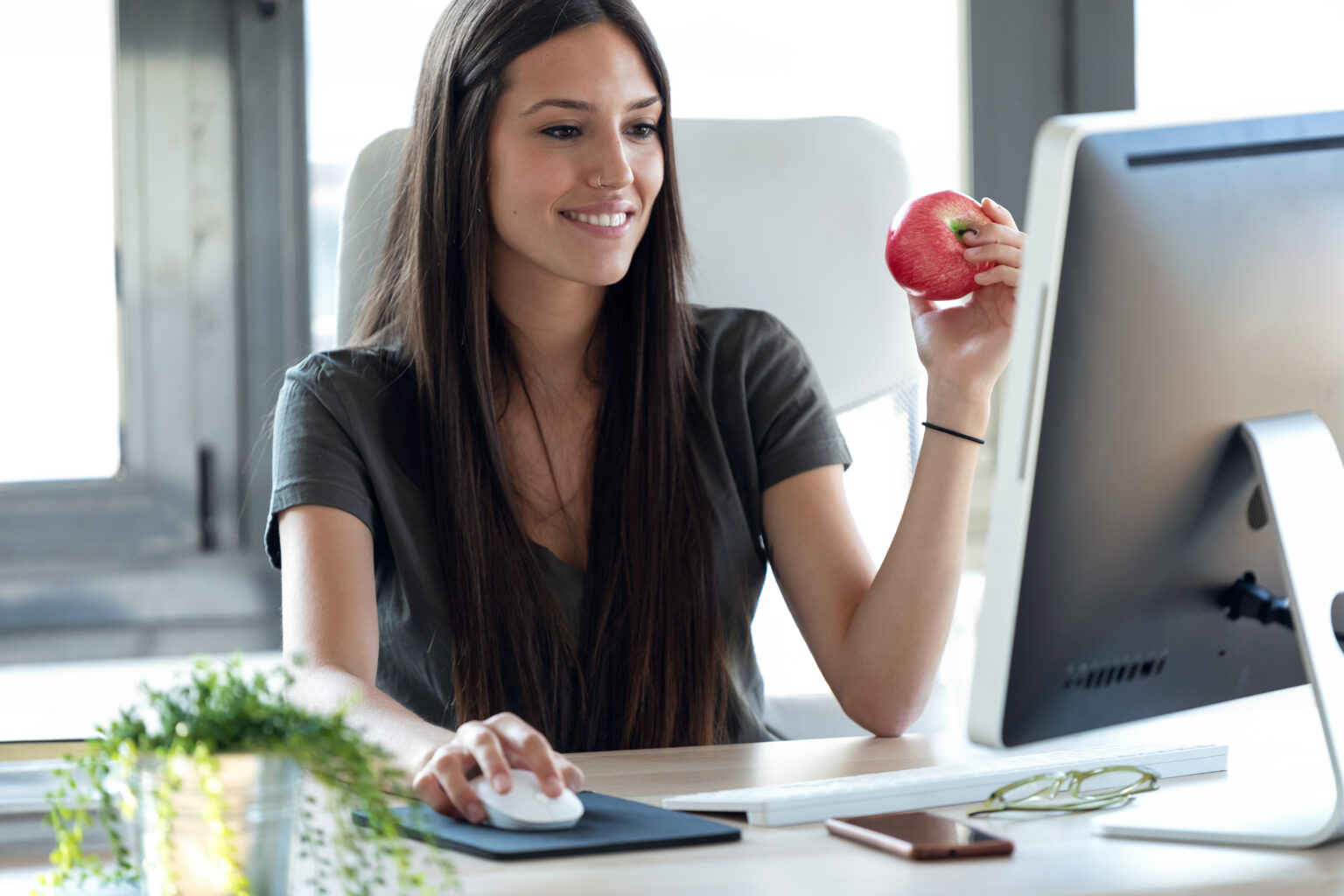 Shot of smiling young business woman eating a red apple while working with computer in the office.