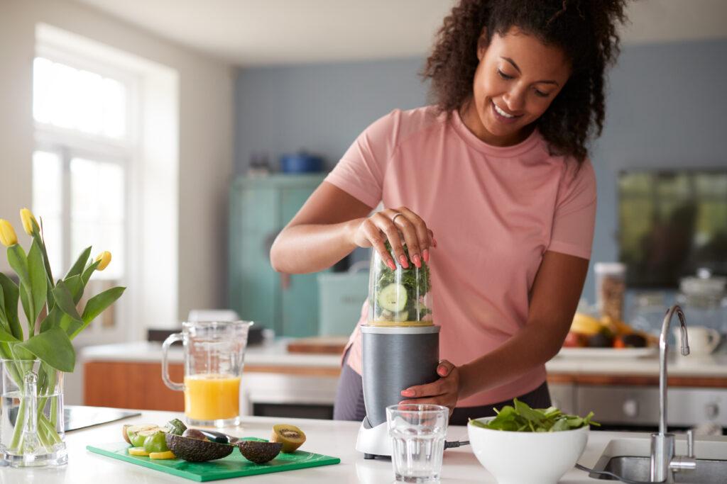 Mulher preparando vitamina para aumentar a imunidade